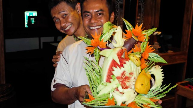 Anto and Putu, the steward and chef, showing off Putu's carving skills